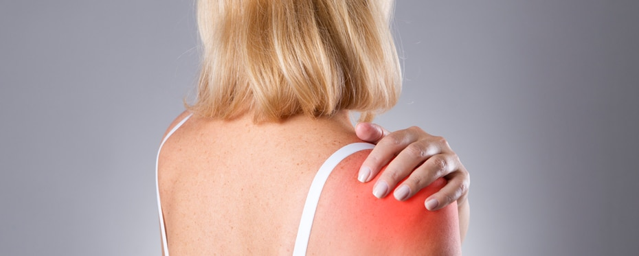 A woman holding her painful shoulder