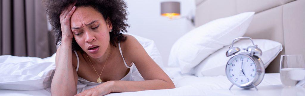 A sleepless woman lies awake next to an alarm clock