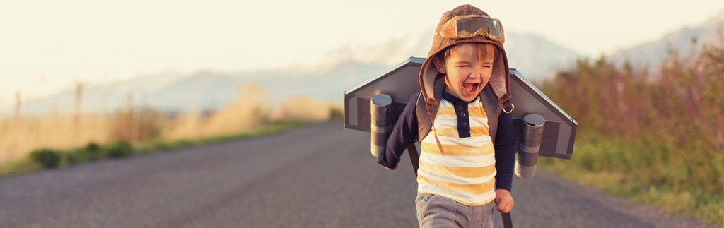 a toddler runs down a road in a rocket costume