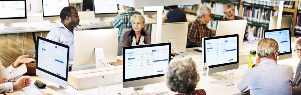 members of the public use computers in a public library