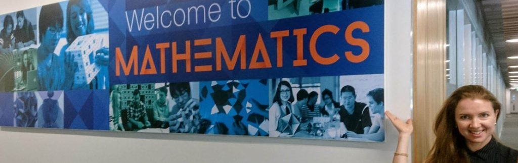 Dr Tanya Evans in front of a 'Welcome to Mathematics' sign