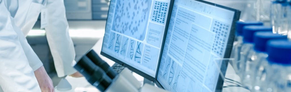 a scientist looks at data upon a screen