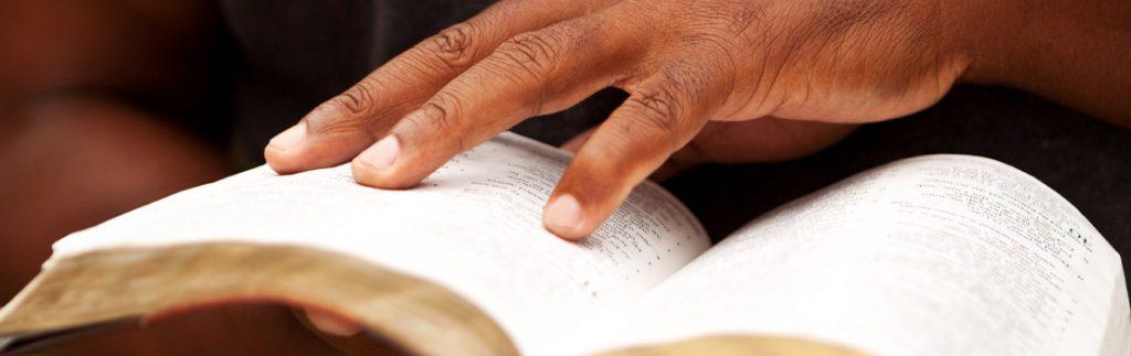 a hand pores over an open book